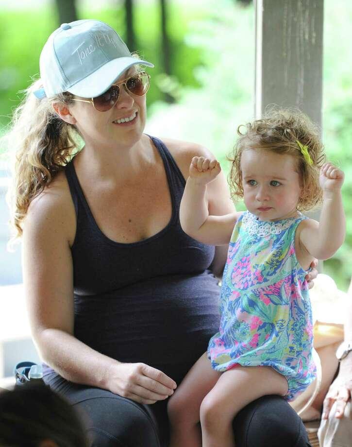 Greenwich's Maureen Corbo and her daughter, Millie, 1, enjoy a children's book reading at the Greenwich Library Stories in the Park program at the Bruce Park Playground gazebo across the street from the Bruce Museum in Greenwich, Conn. Wednesday, July 11, 2018. Dozens of children and their caretakers crowded into the gazebo for readings of children's books and interactive songs for babies, toddlers, and preschoolers. Photo: Tyler Sizemore / Hearst Connecticut Media / Greenwich Time