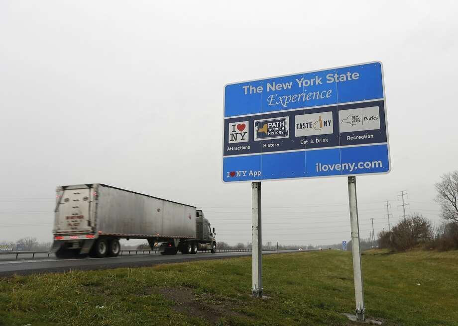 "FILE - In this Nov. 29, 2016, file photo, a truck passes a sign proclaiming ""I Love New York"" and marketing other state attractions on the New York State Thruway in Utica, N.Y. The 500-plus tourism signs the Cuomo administration has installed along expressways from Long Island to Buffalo are at the center of a years-long spat between the Federal Highway Administration (FHWA) and Democratic Gov. Andrew Cuomo. The agency says the signs pose a potential distraction to drivers traveling at high speeds and has told the state to remove them by Sept. 30 or lose $14 million in federal highway funding. No signs have been removed so far. (AP Photo/Mike Groll, File) Photo: Mike Groll, Associated Press"