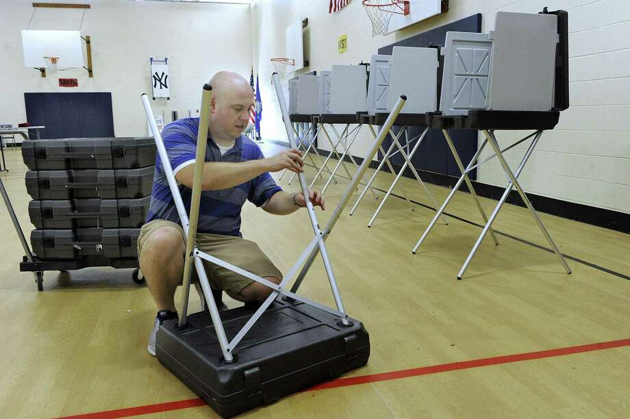 Ryan Murphy, Republican registrar of voters in Brookfield, sets up the Huckleberry Hill School polling place for Tuesday's referendum on the town's capital budget. Polls are open in Brookfield from 6 a.m. to 8 p.m. for the vote on the $2.15 million capital plan, which includes various projects such as road paving, handicap-accessible bathrooms at the library, upgrades to the Parks and Recreation maintenance building and renovations to the boys' locker room at the high school. District I votes at Huckleberry Hill Elementary School, while District II votes at Center Elementary School. The latter is a different polling place than usual because water is shut off at the high school due to a tank replacement. Photo: Carol Kaliff / Hearst Connecticut Media / The News-Times