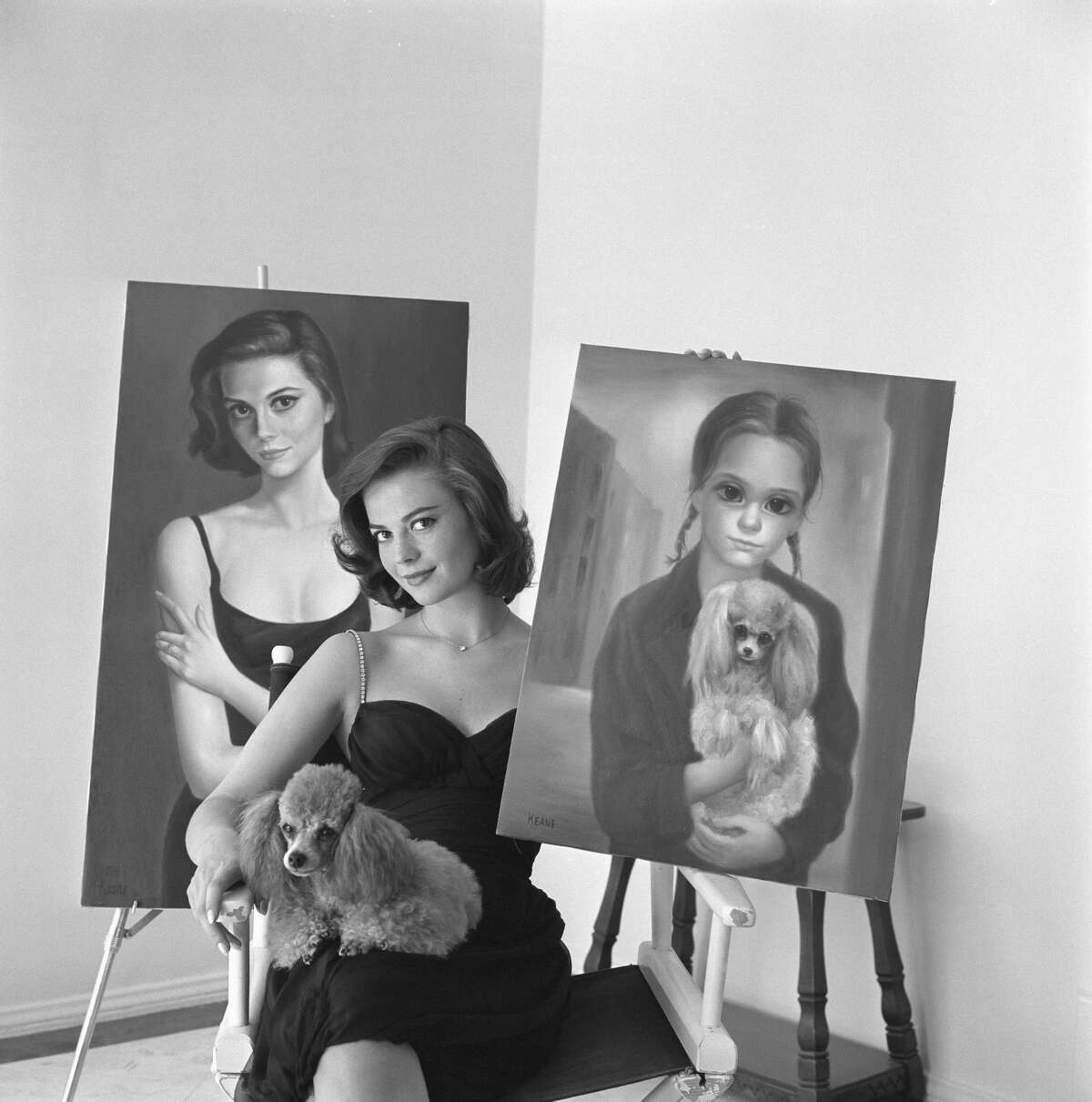 """FILE-- Natalie Wood displays the two portraits which visitors to her Bel Air, Calif., home assume were painted many years apart. Actually, they were painted at the same time in joint sessions with Margaret and Walter Keane, a man-and-wife artist team from San Francisco. Margaret transferred the actress to canvas as a pensive, sophisticated woman. Walter portrayed her as a wistful, wide-eyed waif. Natalie holds Rembrandt, the pooch she is holding in the gamin portrait. Even the dog has been """"interpreted."""""""