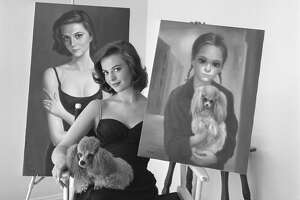 """(Original Caption) Double Image. Bel Air, California: Natalie Wood displays the two portraits which visitors to her Bel Air, California, home assume were painted many years apart. Actually, they were painted at the same time in joint sessions with Margaret and Walter Keane, a man-and-wife artist team from San Francisco. Margaret transferred the actress to canvas as a pensive, sophisticated woman. Walter portrayed her as a wistful, wide-eyed waif. Natalie holds Rembrandt, the pooch she is holding in the gamin portrait. Even the dog has been """"interpreted."""""""