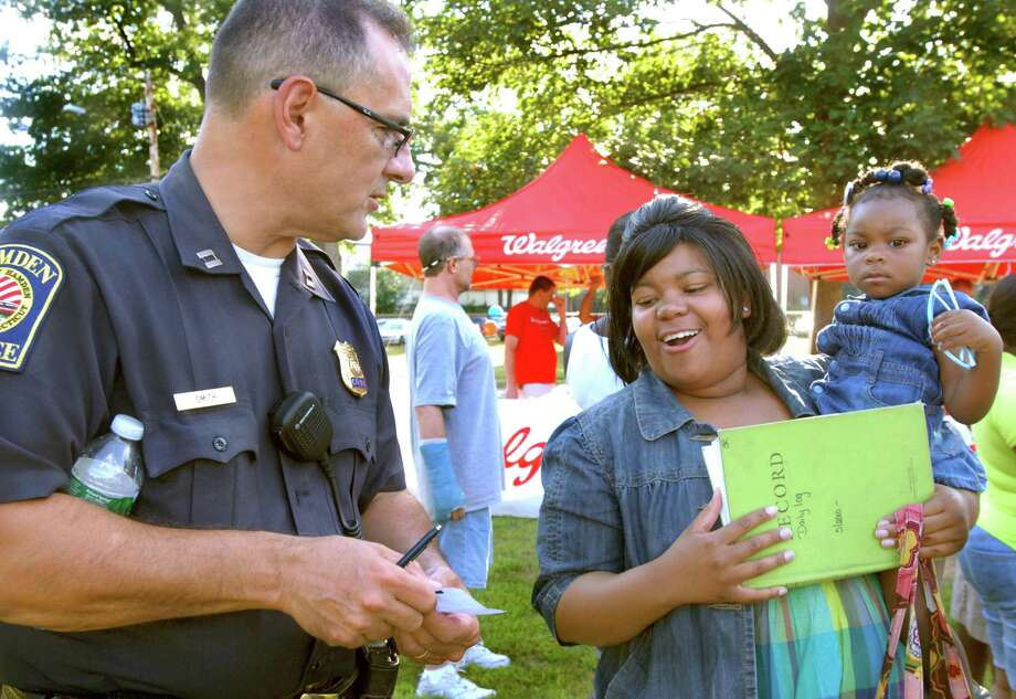 Hamden Police Capt. Ronald Smith (L) discusses internship possibilities with criminal justice major Shanelle Robinson at a previous  National Night Out in Hamden. Photo: Hearst Connecticut Media File