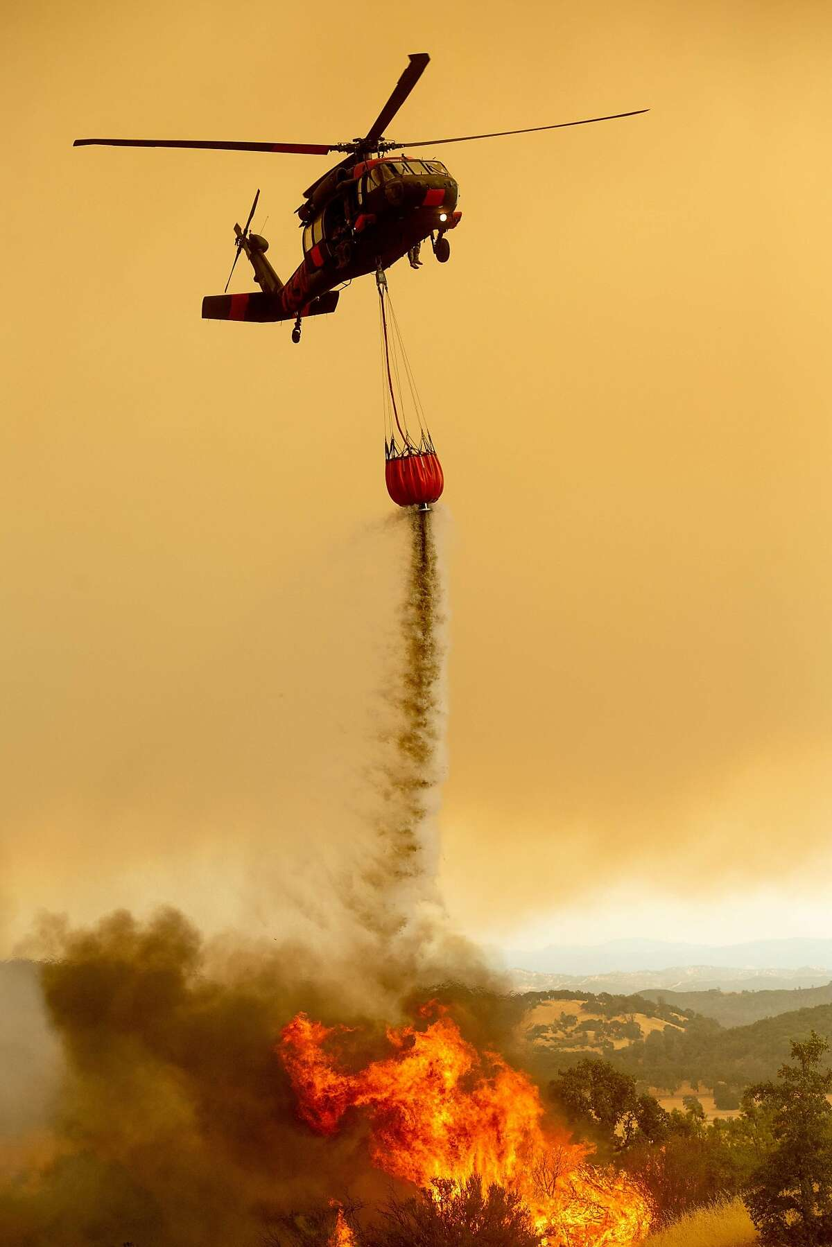A helicopter drops water on the Ranch Fire, part of the Mendocino Complex Fire, burning on High Valley Rd. near Clearlake Oaks, California, on Sunday, Aug. 5, 2018. / AFP PHOTO / NOAH BERGERNOAH BERGER/AFP/Getty Images