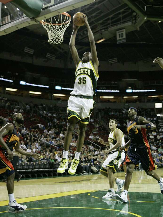 Seattle SuperSonics forward Kevin Durant dunks in the second quarter of an NBA basketball exhibition game as Golden State Warriors' Baron Davis, left, and Al Harrington, right, look on along with Sonics' Wally Szczerbiak, second from right, Tuesday, Oct. 23, 2007, at KeyArena in Seattle. Durant is the focal point of the 2007 SuperSonics, who open their season on Oct. 31 at Denver with a remodeled roster minus it's two leading scores from a year ago, and a franchise rife with off-court questions about its future. Photo: Ted S. Warren / Associated Press / AP2007