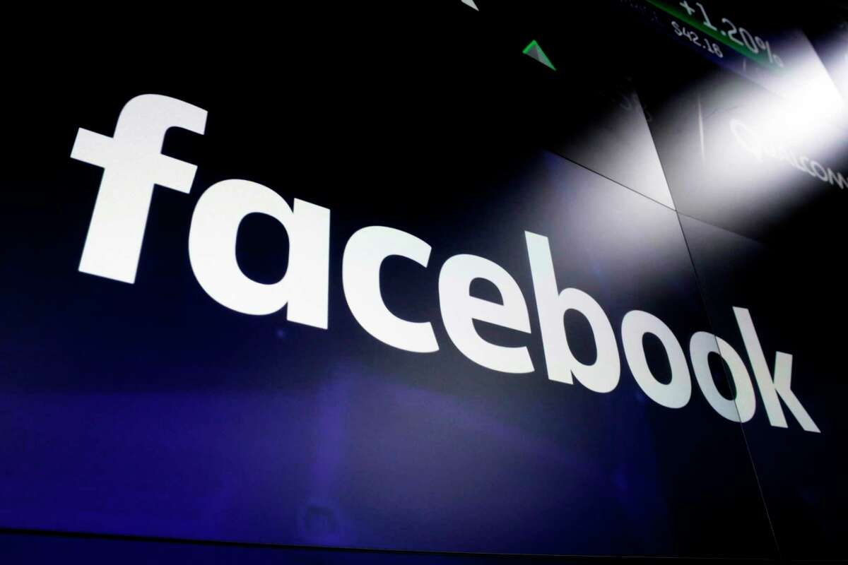 This March 29, 2018, photo shows the logo for Facebook appears on screens at the Nasdaq MarketSite, in New York's Times Square. With less than three months to go before the midterm elections, Facebook is enforcing strict new requirements on digital political ads. Among other things, they force political ad buyers to verify their identities by receiving mail at a known U.S. address. (AP Photo/Richard Drew)