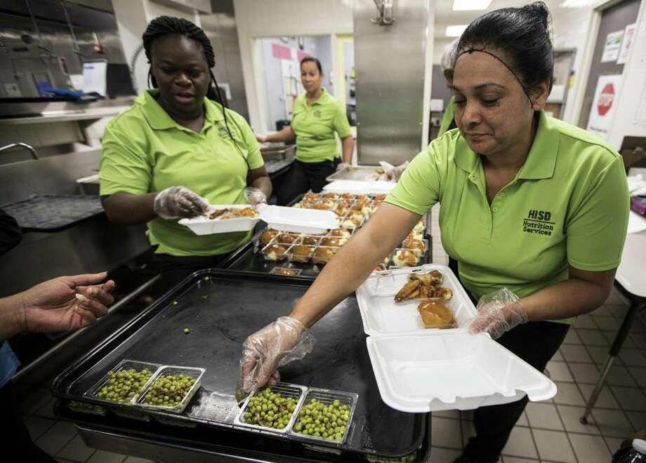 Larie Young, left, and Sonia Herrera prepare meals for the community at Shadydale Elementary School in 2017.
