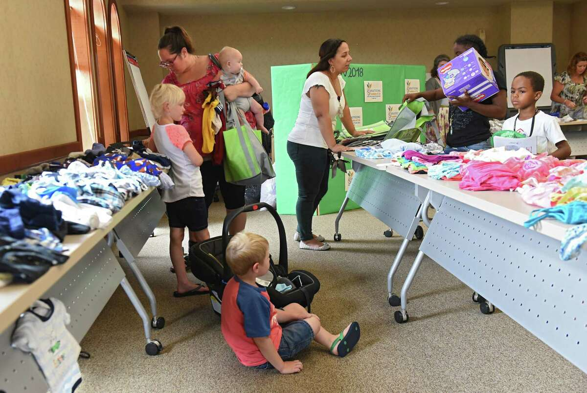 Mothers and pregnant women look through donated clothes as the Troy Baby CafŽ celebrates it's first anniversary at the Commission on Economic Opportunity (CEO) Community Resource Center Friday, Aug. 3, 2018 in Troy, N.Y. (Lori Van Buren/Times Union)