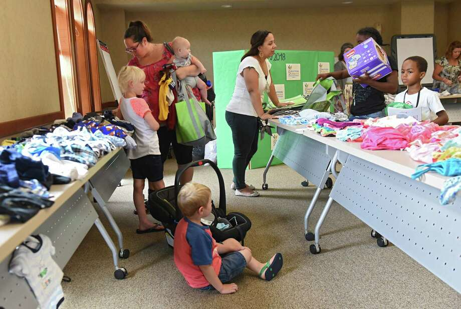 Mothers and pregnant women look through donated clothes as the Troy Baby CafŽ celebrates it's first anniversary at the Commission on Economic Opportunity (CEO) Community Resource Center Friday, Aug. 3, 2018 in Troy, N.Y. (Lori Van Buren/Times Union) Photo: Lori Van Buren / 20044451A