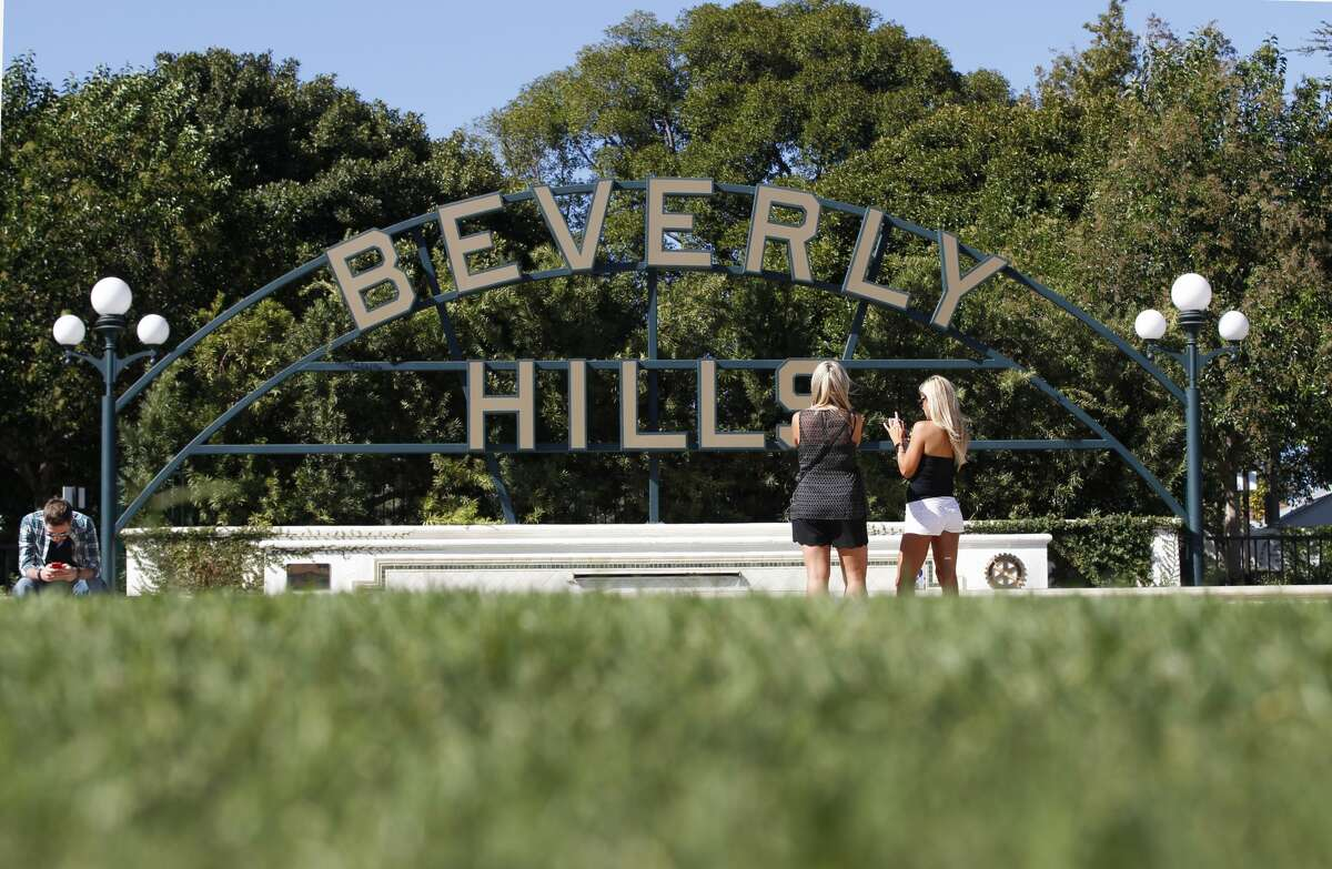 BEVERLY HILLS, CALIF. -- FRIDAY, OCTOBER 30, 2015: Tourists view their photos of the Beverly Hills sign in Beverly Gardens Park, Beverly Hills Friday, Oct. 30, 2015. Photos taken in Beverly Hills, Calif., on Oct. 30, 2015. The city of Beverly Hills and three other water suppliers face financial penalties for falling short of state water conservation mandates, officials said Friday. Statewide, Californians cut their urban water use in September by 26.1% compared with the same month in 2013, regulators said. The reduction was below the 27% decline recorded in August and the 31% savings in July. In addition to Beverly Hills, the cities of Indio and Redlands and the Coachella Valley Water District were issued a $61,000 penalty for failing to meet their conservation mandates, officials said. (Photo by Allen J. Schaben / Los Angeles Times via Getty Images)