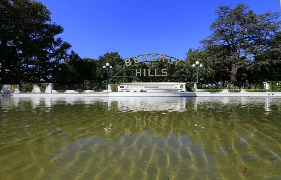 BEVERLY HILLS, CALIF. -- FRIDAY, OCTOBER 30, 2015: A water fountain flows by the Beverly Hills sign in Beverly Gardens Park, Beverly Hills Friday, Oct. 30, 2015. The city of Beverly Hills and three other water suppliers face financial penalties for falling short of state water conservation mandates, officials said Friday. Statewide, Californians cut their urban water use in September by 26.1% compared with the same month in 2013, regulators said. The reduction was below the 27% decline recorded in August and the 31% savings in July. In addition to Beverly Hills, the cities of Indio and Redlands and the Coachella Valley Water District were issued a $61,000 penalty for failing to meet their conservation mandates, officials said. (Photo by Allen J. Schaben / Los Angeles Times via Getty Images)