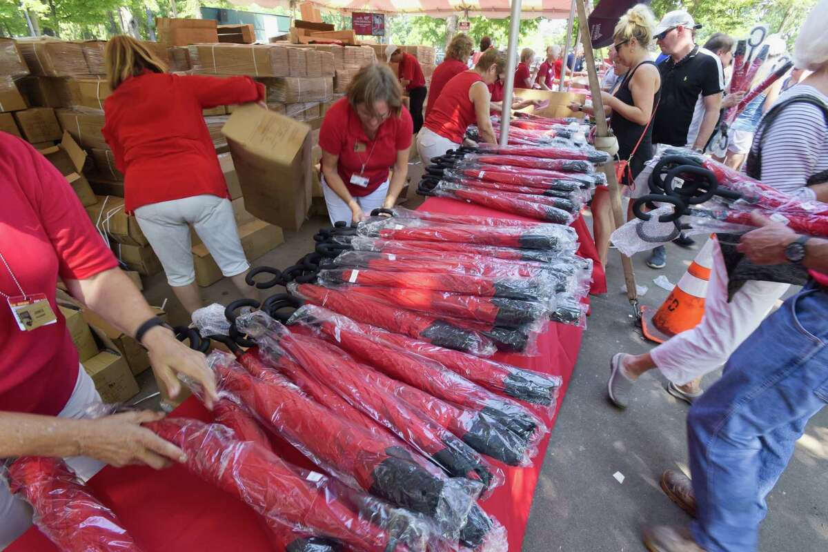 Workers hand out umbrellas as the give away for entrance at the Saratoga Race Course on Monday, Aug. 6, 2018, in Saratoga Springs, N.Y. (Paul Buckowski/Times Union)