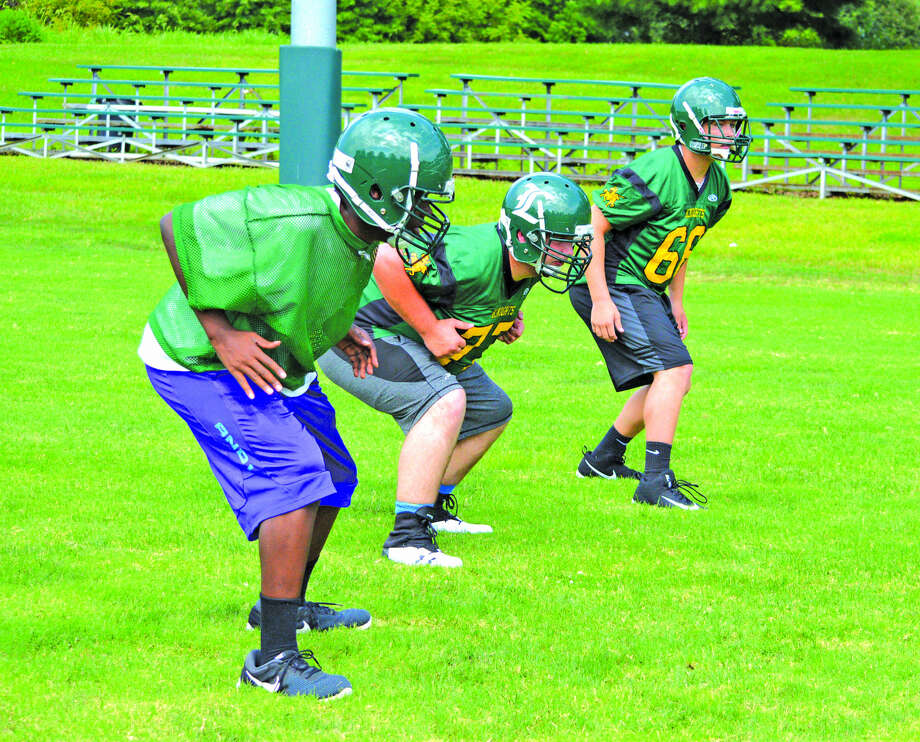 A trio of Metro-East Lutheran linemen perform a drill on Monday, which was the first official practice for the Knights. Metro was 1-8 last season under first-year Micah Pomerenke, with its only win coming on a forfeit. Photo: Scott Marion