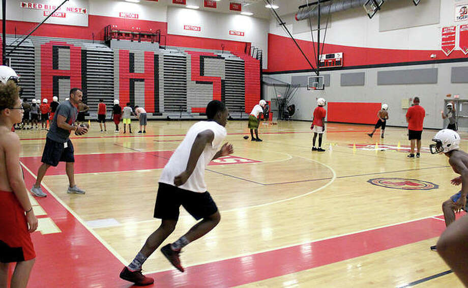 Alton High football coach Eric Dickerson, far left, gets set to throw a pass during a drill Monday evening in the AHS gym. A thunderstorm that rolled through the area Monday, forced part of the Redbirds; first practice inside. Photo:     Pete Hayes | The Telegraph