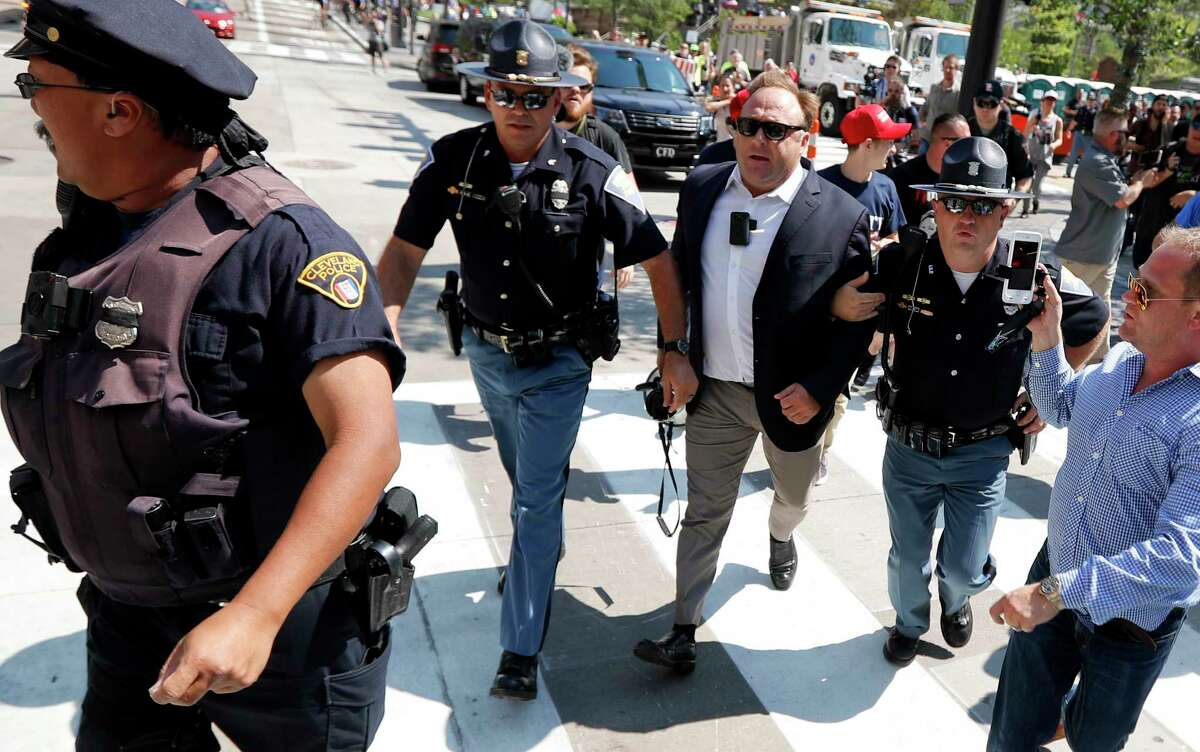 FILE - In this Tuesday, July 19, 2016 file photo, Alex Jones, center right, is escorted by police out of a crowd of protesters outside the Republican convention in Cleveland. Facebook says it has taken down four pages belonging to conspiracy theorist Alex Jones for violating its hate speech and bullying policies. The social media giant said in a statement Monday, Aug. 6, 2018 that it also blocked Jones' account for 30 days because he repeatedly posted content that broke its rules. (AP Photo/John Minchillo, File)