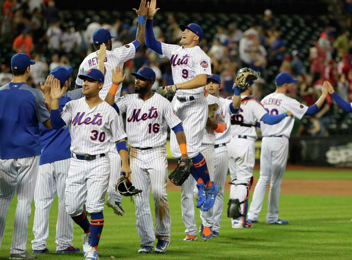 New York Mets' Michael Conforto (30), Austin Jackson (16) and Brandon Nimmo (9) celebrate with teammates after a baseball game against the Cincinnati Reds Monday, Aug. 6, 2018, in New York. The Mets won 6-4. (AP Photo/Frank Franklin II)