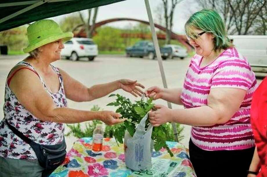 A sale is made at the Midland Area Farmers Market. (Daily News File Photo)