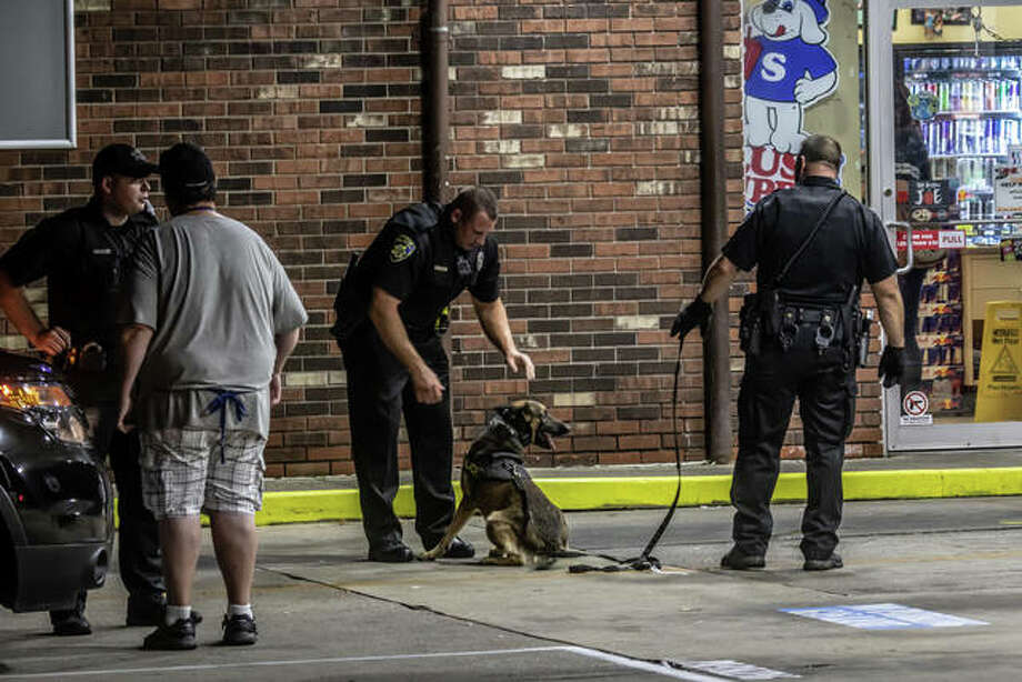 A police dog gets a satisfying pat on the head after an extensive search of the area early Tuesday morning following the armed armed robbery of the Hit N Run gas station at 2345 State St. in Alton.