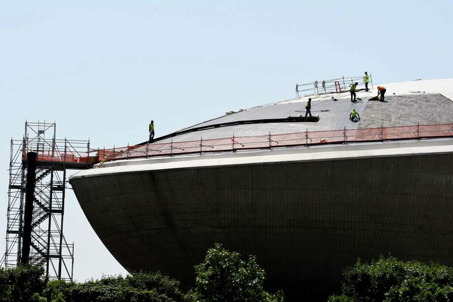 Workers replace the roof of The Egg on Monday, Aug. 6, 2018, at the Empire State Plaza in Albany, N.Y. The $4.4 million roof replacement project is expected to be completed next year. This is the first time the roof has been replaced since the facility opened in 1978. (Will Waldron/Times Union) Photo: Will Waldron