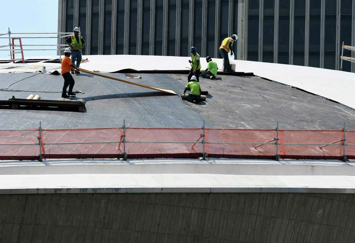 Workers replace the roof of The Egg on Monday, Aug. 6, 2018, at the Empire State Plaza in Albany, N.Y. The $4.4 million roof replacement project is expected to be completed next year. This is the first time the roof has been replaced since the facility opened in 1978. (Will Waldron/Times Union)