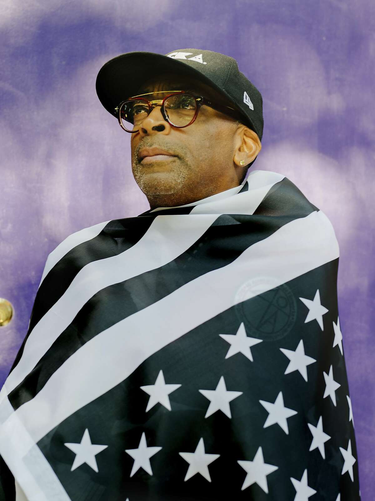 """Director Spike Lee drapes himself in an upside-down, black-and-white American flag in New York, July 20, 2018. In """"BlacKkKlansman,"""" Lee uses the true story of a black police officer infiltrating the Ku Klux Klan in Colorado in the 1970s to once again grapple with American racial terrorism. """"We're living in pure, undiluted insanity,"""" he said. (Heather Sten/The New York Times)"""
