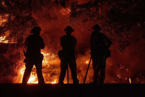 Firefighters watch a back burn during the Mendocino Complex fire in Upper Lake, California on July 31, 2018. - The Mendocino Complex -- made up of two fires -- has burned more than 24,000 acres in total since July 27. Thousands of firefighters in California made some progress against several large-scale blazes that have turned close to 200,000 acres (80,940 hectares) into an ashen wasteland, destroyed expensive homes, and killed eight fire personnel and civilians in the most populous US state. (Photo by JOSH EDELSON / AFP) (Photo credit should read JOSH EDELSON/AFP/Getty Images) *** BESTPIX ***