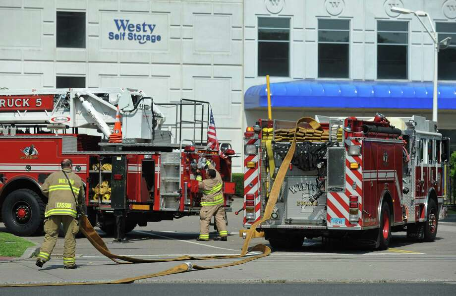 Wilton firefighters respond to 59 Danbury Road where a roof fire broke out in the one-story office building next to Westy Self Storage on Tuesday morning August 6, 2018, in Wilton, Conn. Photo: Erik Trautmann / Hearst Connecticut Media / Norwalk Hour
