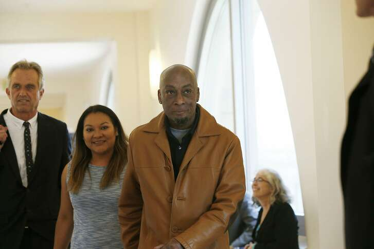 Dewayne Johnson (right), former groundskeeper for the Benicia Unified School District, walks with his wife Araceli Johnson (second from left) through Superior Court of California as they return to Department 504 during the Monsanto trial on Monday, July 23,  2018 in San Francisco, Calif.