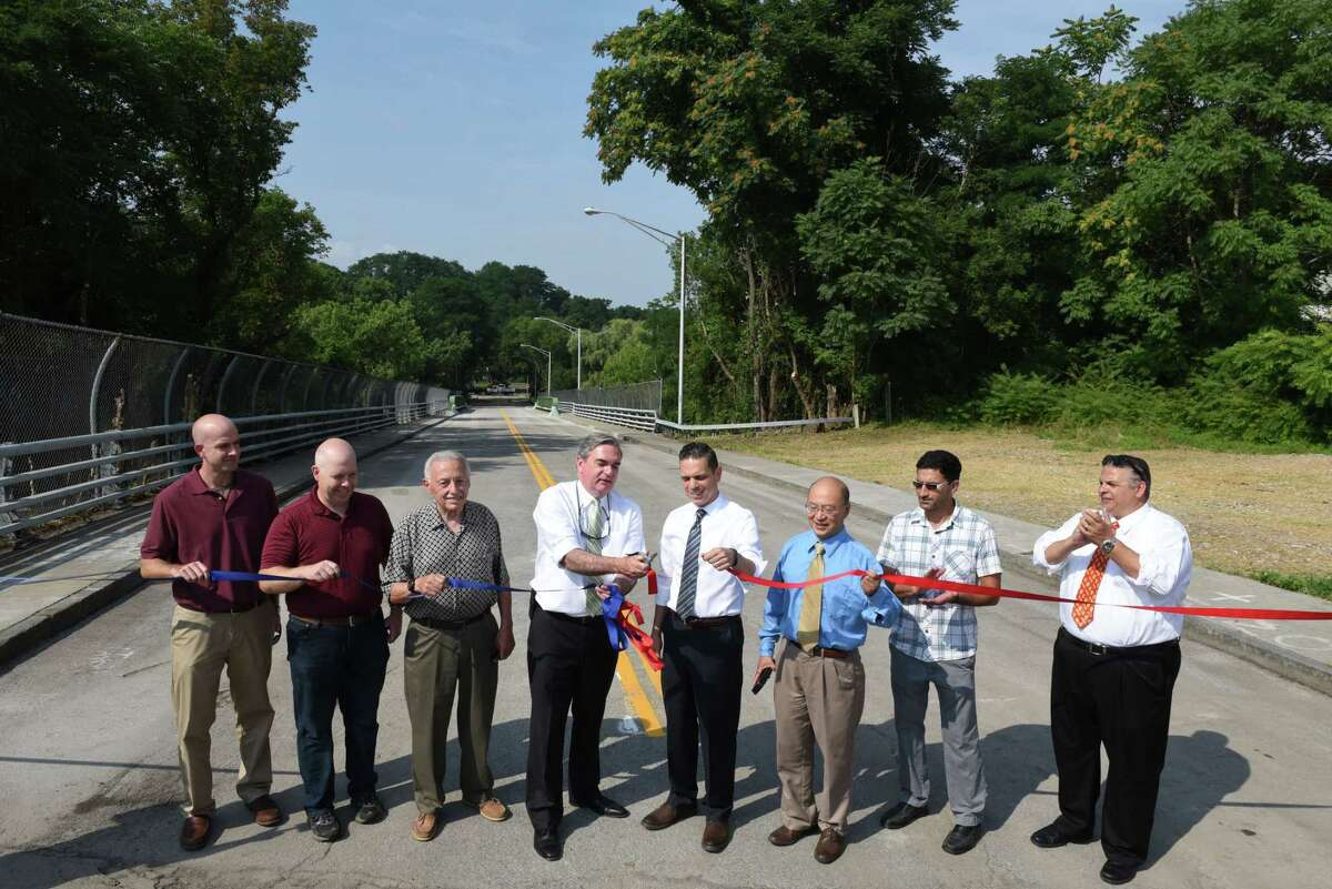 Mayor Gary McCarthy, center left, and Assemblyman Angelo Santabarbara, center right, cut the ribbon to reopen the Oak Street Bridge following a $1.75 million repair project on Tuesday, Aug. 7, 2018, in Schenectady, N.Y. The bridge, which connects the Mont Pleasant and Bellevue neighborhoods of Schenectady, was closed to traffic for five years. (Will Waldron/Times Union)