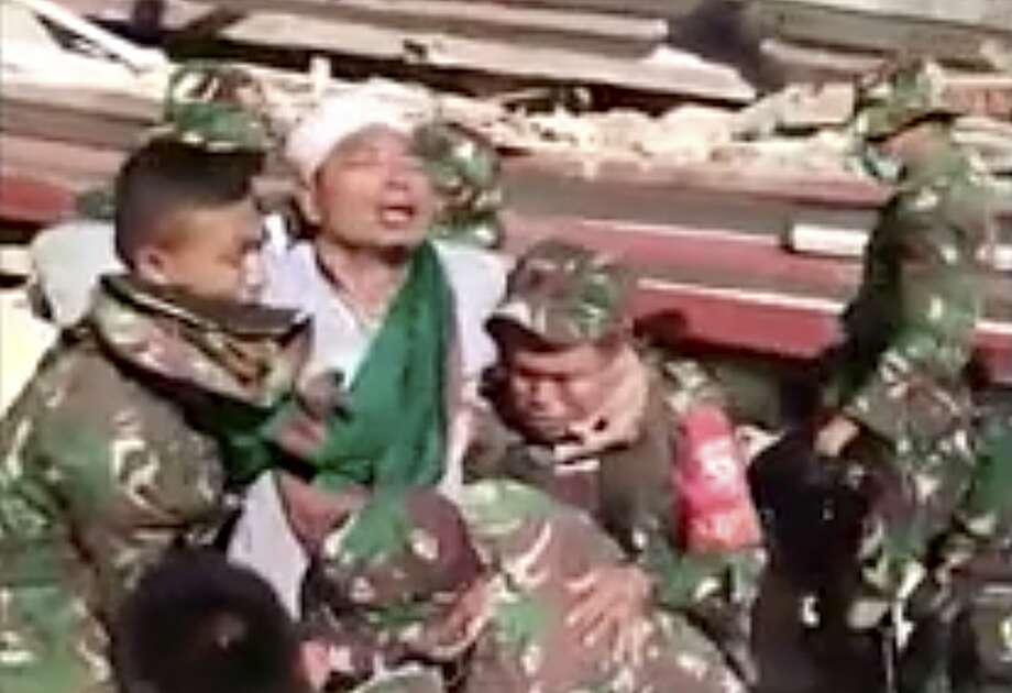 TV footage shows soldiers carrying a man rescued from a mosque destroyed in Sunday's earthquake. Photo: Ivan Fadillah / Indonesia Military