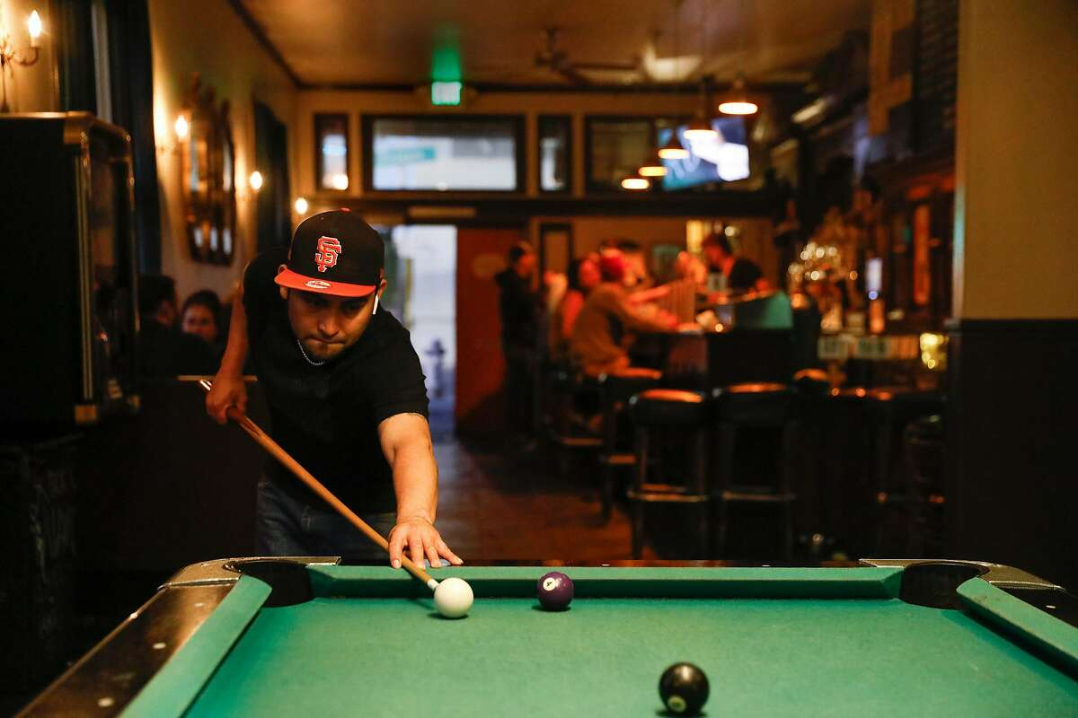 Sergio Villanueva (SF ball cap) playing a game of pool at Wooden Nickel, a dive bar in the Mission district as seen in San Francisco, California, on August 6, 2018.