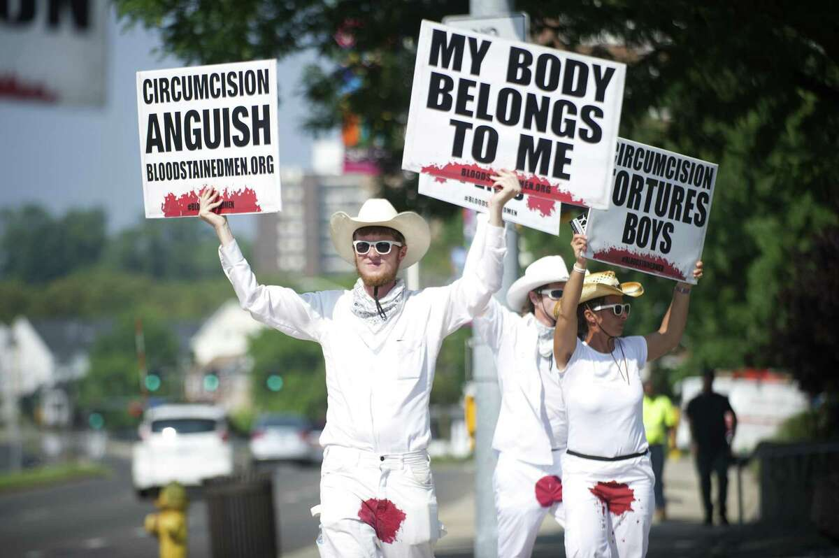 Non-profit group Bloodstained Men member David Atkinson of Boston, center, holds anti-circumcision signs while protesting at the intersection of Washington Blvd. and Tresser Blvd. in downtown Stamford, Conn. on Tuesday, Aug. 7, 2018. The group, which is currently in the middle of a 21 city tour, calls the process unnecessary and destructive while attempting to raise awareness and educate the public on the issue.