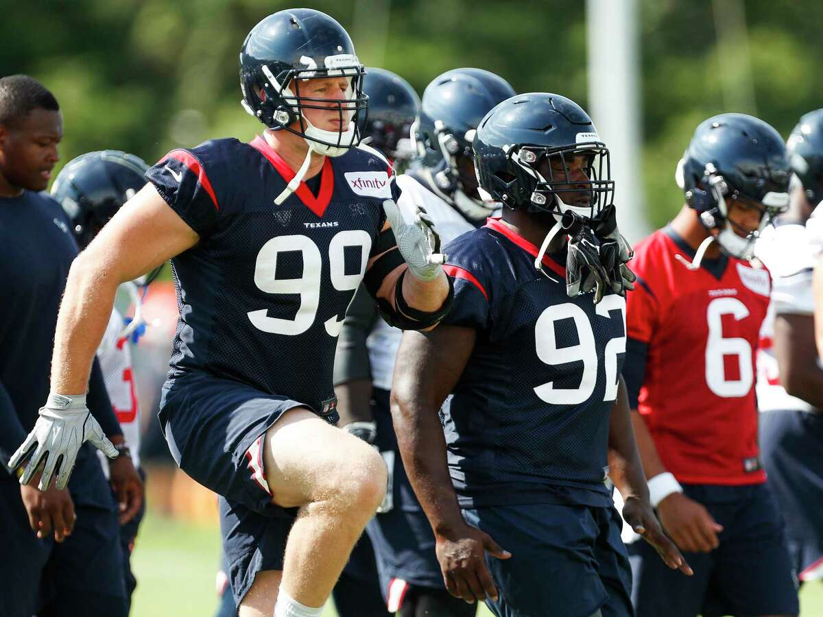 Houston Texans defensive end J.J. Watt (99) and defensive tackle Brandon Dunn (92) warm up during training camp at the Greenbrier Sports Performance Center on Tuesday, Aug. 7, 2018, in White Sulphur Springs, W.Va.