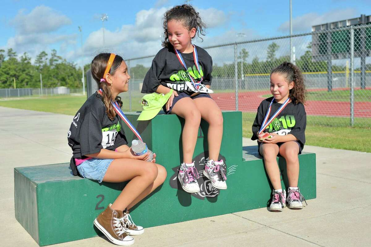 The Elementary Girls medalists chat while sitting on the medal stand.