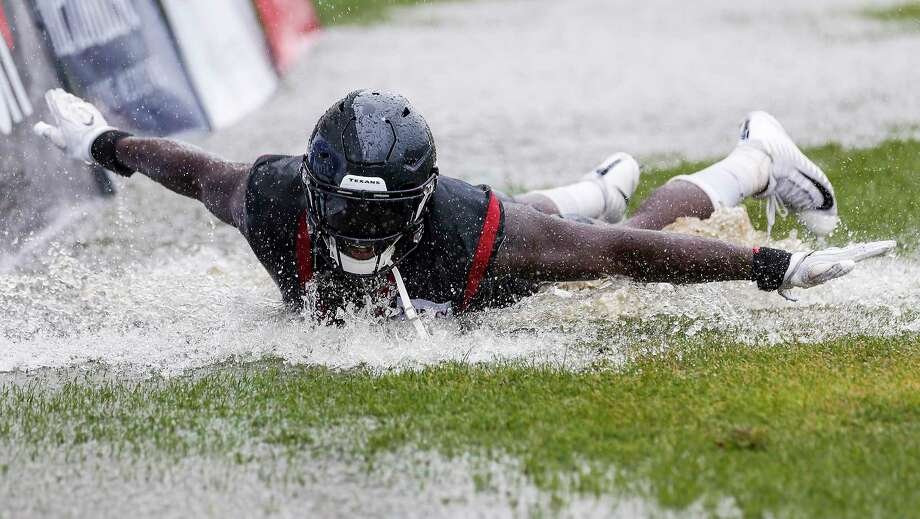 Houston Texans linebackers Whitney Mercilus (59) slides in a puddle of water on the field at the end of practice during training camp at the Greenbrier Sports Performance Center on Friday, Aug. 3, 2018, in White Sulphur Springs, W.Va. A steady rain fell throughout practice. Photo: Brett Coomer, Houston Chronicle / © 2018 Houston Chronicle