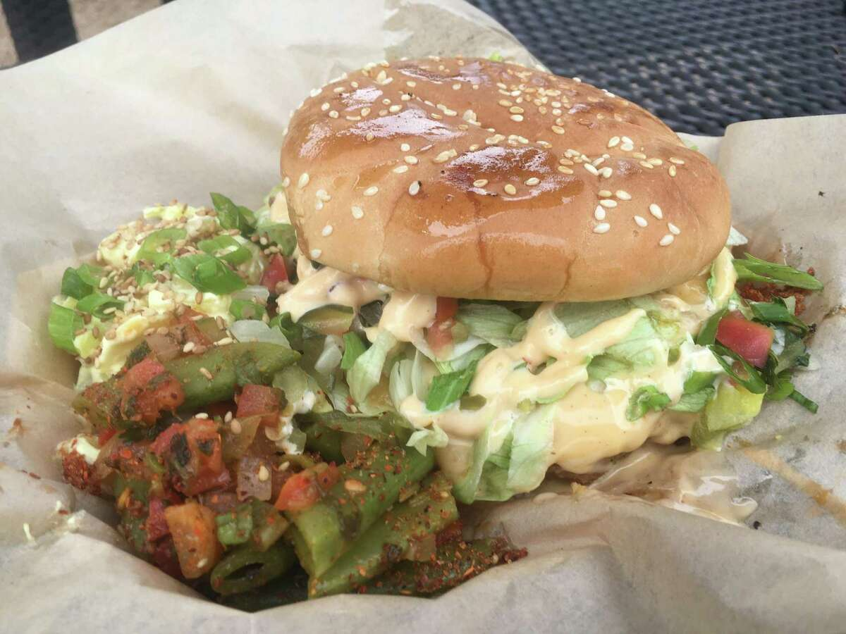 """The Monster Chicken Fried Cheeseburger at the Guerrilla Gourmet food truck sells for $10 and includes two side items. It's an 8 ounce patty topped with shredded lettuce, """"pickle de gallo,"""" cheese gravy, jalapeños, the special house """"guerilla sauce."""""""