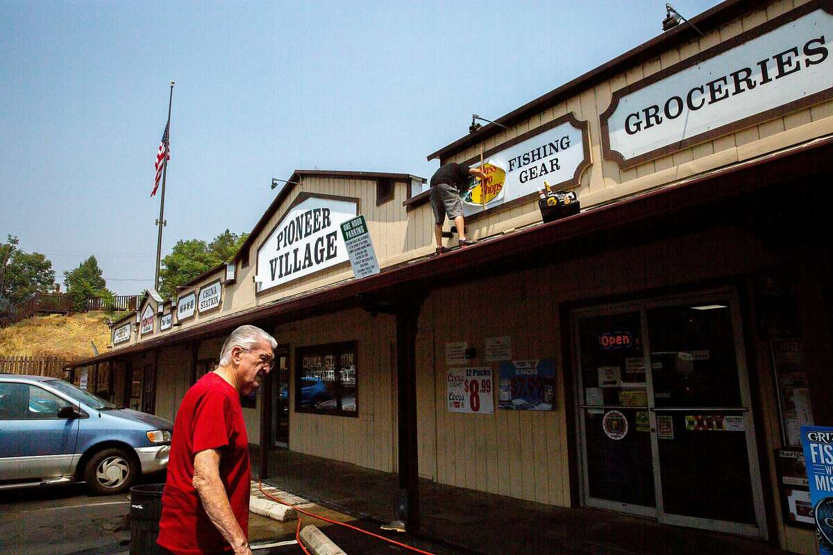 From left: Sam Pioske heads into the groceries store as Tim Hooper puts up a new sign, Tuesday, Aug. 7, 2018, in Mariposa, Calif.