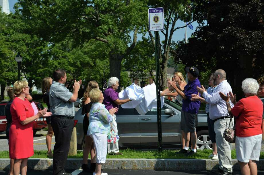 Guests applaud during the unveiling of a sign that marks the designated parking place reserved for Purple Heart recipients during a ceremony at City Hall. Photo: Leslie Hutchison / Hearst Connecticut Media /