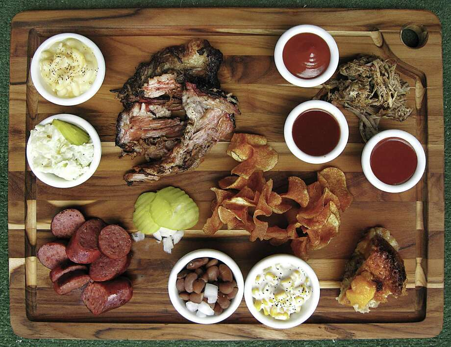 Barbecue and sides from Crossroads BBQ. Clockwise from top left: mac and cheese, brisket, tangy barbecue sauce, regular barbecue sauce, spicy barbecue sauce, pulled pork, peach cobbler, creamed corn, pinto beans, sausage, potato salad and house-fried potato chips. Photo: Mike Sutter /Staff