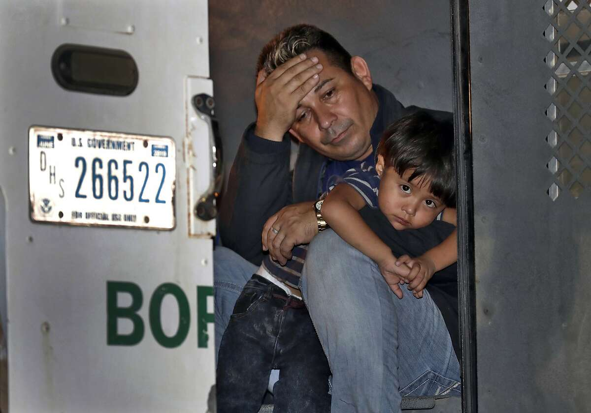 A father and his 3-year-old son are detained in the back of a U.S. Customs and Border Patrol vehicle Wednesday, July 18, 2018 in San Luis, Ariz. The boy, his father and two siblings were arrested by a U.S. Border Patrol agent who spotted them crossing a canal along the the international border. (AP Photo/Matt York)