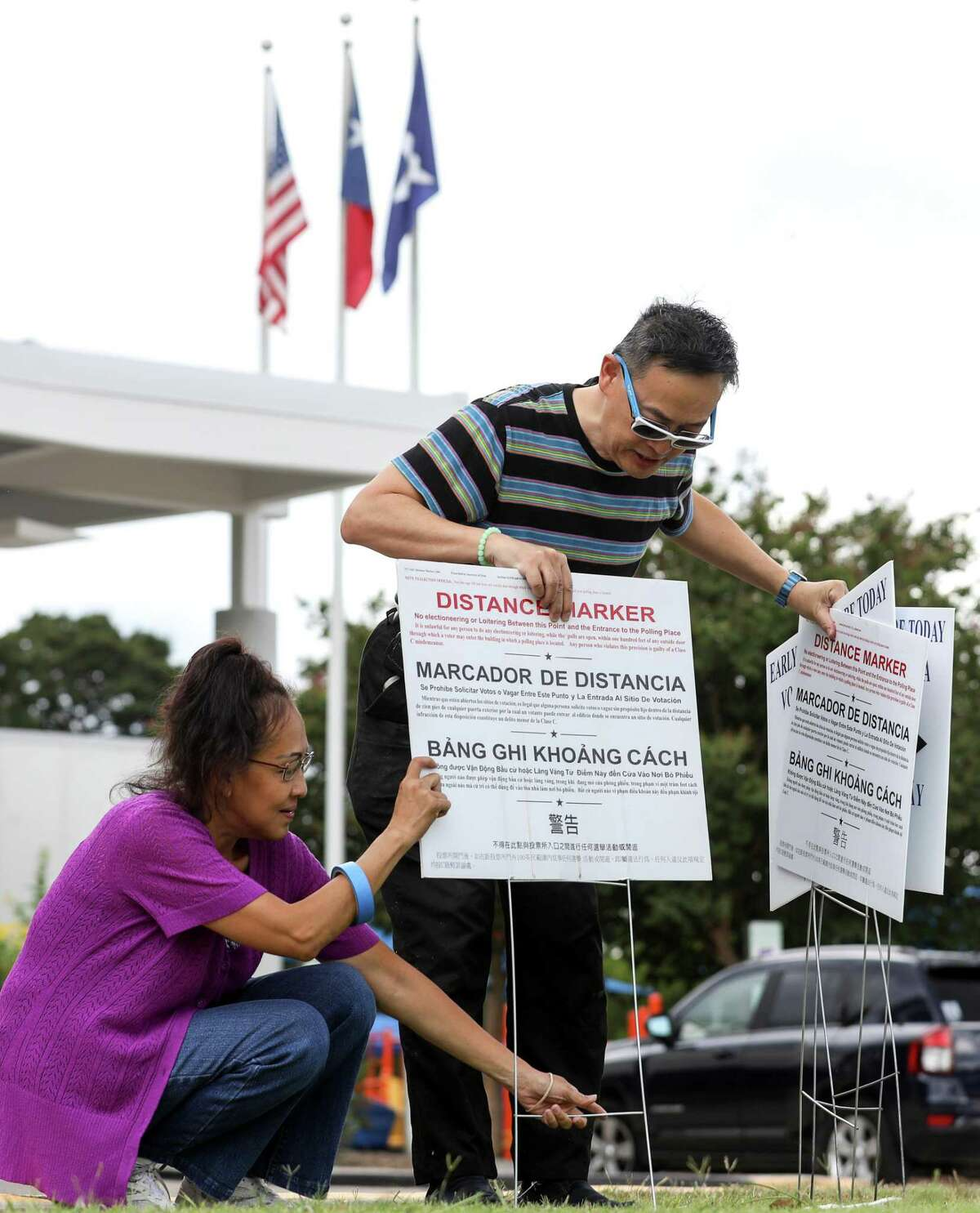 Kyle Fu, right, and Kathy Huynh set up a voting location at the West Gray Metropolitan Multi-Services Center Tuesday, Aug. 7, 2018, in Houston.