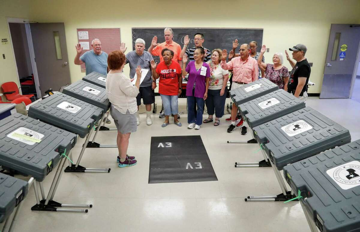 Katie Gray, an early voting judge, administers the oath to a group of election workers at the West Gray Metropolitan Multi-Services Center Tuesday, Aug. 7, 2018, in Houston.