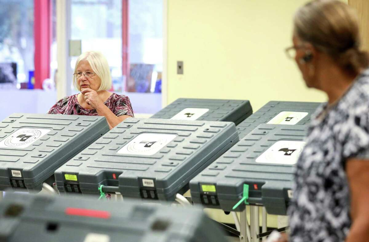 Mae Huckabay, left, works to set up a voting location at the West Gray Metropolitan Multi-Services Center Tuesday, Aug. 7, 2018, in Houston.