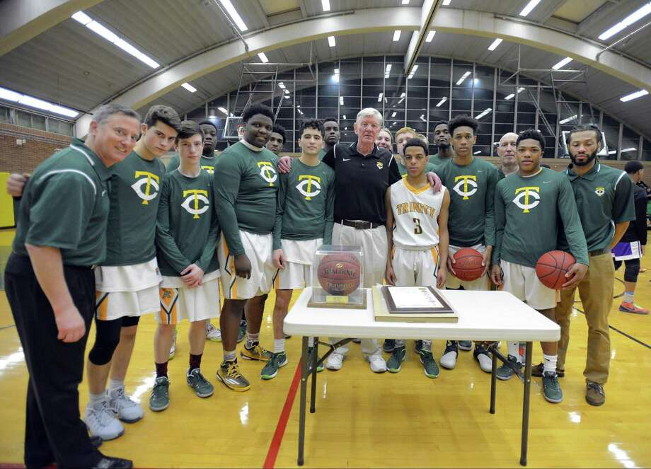 Trinity Catholic High School players and coaches gather around a game ball and City of Stamford Proclamation that was presented at Trinity Catholic High School's Walsh Court in Stamford, Conn. on Jan. 20, 2017 to coach Mike Walsh, center, for his 600th win. Walsh, who is in his 38th season as head coach for the Crusaders, earned his 600th win on Jan 3, 2017 after defeating St. Joseph High School in a FCIAC boys basketball game. Photo: Matthew Brown / Hearst Connecticut Media / Stamford Advocate