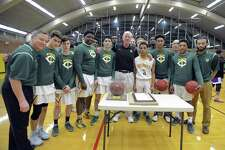Trinity Catholic High School players and coaches gather around a game ball and City of Stamford Proclamation that was presented at Trinity Catholic High School's Walsh Court in Stamford, Conn. on Jan. 20, 2017 to coach Mike Walsh, center, for his 600th win. Walsh, who is in his 38th season as head coach for the Crusaders, earned his 600th win on Jan 3, 2017 after defeating St. Joseph High School in a FCIAC boys basketball game.