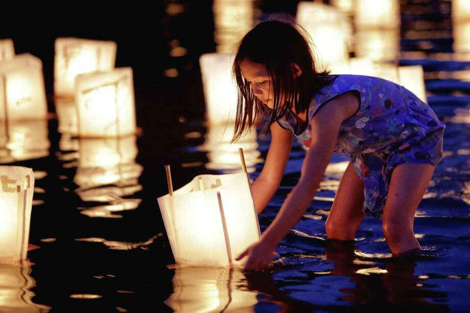 Sophia Barbagelapa, 7, floats a paper lantern in the water as people gather Monday at Green Lake to honor victims of the atomic bombings of Hiroshima, Nagasaki and other wars. Thousands gathered on a dock and the shore of Green Lake on the 73rd anniversary of the U.S. use of the atomic bomb to launch floating lanterns. The date has been marked with a ceremony at Green Lake since 1984. Photographed on Aug. 6, 2018. Photo: GENNA MARTIN, SEATTLEPI.COM / SEATTLEPI.COM