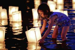 Sophia Barbagelapa, 7, floats a paper lantern in the water as people gather Monday at Green Lake to honor victims of the atomic bombings of Hiroshima, Nagasaki and other wars. Thousands gathered on a dock and the shore of Green Lake on the 73rd anniversary of the U.S. use of the atomic bomb to launch floating lanterns. The date has been marked with a ceremony at Green Lake since 1984. Photographed on Aug. 6, 2018.