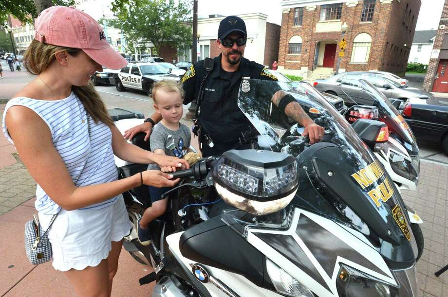 3 yr-old Will McStay gets a feel for a police motorcycle as his mom Caitlyn helps him reach handlebars as Norwalk Police Motorcycle Patrol Officer Chris Wasilewski watches, during National Night Out at Police headquarters on Tuesday August 7, 2018 in Norwalk Conn.The event is an evening of community building to promote police-community partnerships and neighborhood camaraderie. Hosted by the Norwalk Police Department, the family-friendly event is  featured free food, games, music and a chance to get to know your local officers. Photo: Alex Von Kleydorff / Hearst Connecticut Media / Norwalk Hour