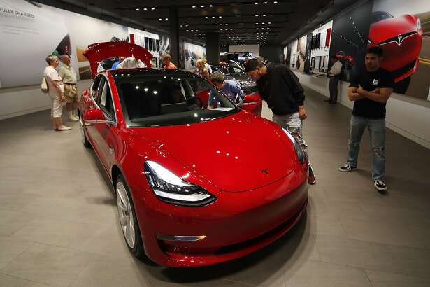 "In this Friday, July 6, 2018, photograph, prospective customers confer with sales associates as a Model 3 sits on display in a Tesla showroom in the Cherry Creek Mall in Denver. The Insurance Institute for Highway Safety, in a paper titled ""Reality Check,"" issued the warning Tuesday, Aug. 7, 2018, after testing five of the systems from Tesla, Mercedes, BMW and Volvo on a track and public roads. The systems tested, in the Tesla Model 3 and Model S, BMW's 5-Series, the Volvo S-90 and the Mercedes E-Class, are among the best in the business right now and have been rated ""superior"" in previous IIHS tests. David Zuby, the institute's chief research officer, said the systems do increase safety but the tests show they are not 100 percent reliable. (AP Photo/David Zalubowski)"