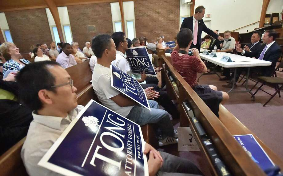 Democratic candidate for Attorney General Paul Doyle of Wethersfield hands off the microphone as both William Tong, of Stamford and Chris Mattei, of Hartford reach for the opportunity to speak Tuesday, August 7, 2018 at a debate hosted by the New Haven Independent and the CT Law Tribune at the Bethel African Methodist Episcopal Church in New Haven. Photo: Catherine Avalone, Hearst Connecticut Media / New Haven Register