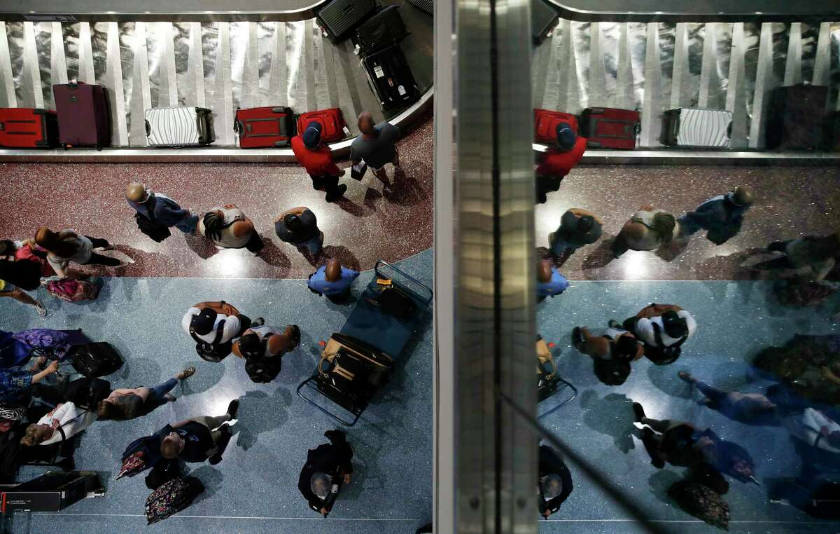 FILE- In this June 29, 2018, photo, passengers wait for baggage at McCarran International Airport in Las Vegas. As summer vacationers start to pack up and head home, Congress is considering a sweeping tally of proposals that could affect travelers, from dictating seat size and legroom to rolling back rules that require airlines to advertise the full price of a ticket. (AP Photo/John Locher, File)
